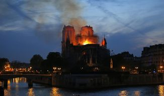 Flames and smoke rise from Notre Dame cathedral in Paris as firefighters tackle the blaze on April 15, 2019. (AP Photo/Michel Euler) ** FILE **