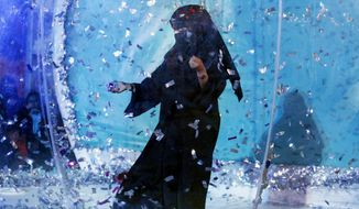 In this Dec. 13, 2019 photo, a woman collects silver tickets as she plays at an amusement park during the Diriyah festival in Diriyah on the outskirts of Riyadh, Saudi Arabia. Hollywood actors, models and social media mavens were invited to Saudi Arabia over the weekend to promote a three-day-long musical festival for young Saudis that took place in the capital, Riyadh. The efforts are aimed at boosting the economy while polishing the country's image abroad and appealing to the young. It's a pivot from just three years ago, when religious police would storm restaurants playing music and harass women in malls for showing their face or wearing red nail polish. (AP Photo/Amr Nabil)