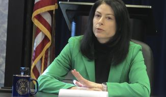 Michigan Attorney General Dana Nessel speaks with reporters about her first year in office on Monday, Dec. 23, 2019, at her office in Lansing, Mich. Nessel says a unique state law is affecting her office's ability to sue over the opioid epidemic, and an investigation into clergy abuse will take longer than the two years she initially projected. (AP Photo/David Eggert)