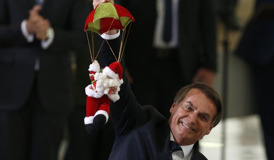 Brazil's President Jair Bolsonaro holds Santa Claus doll on a parachute, during the Christmas celebration with staff and students at the Planalto Presidential Palace, in Brasilia, Brazil, Thursday, Dec. 19, 2019. (AP Photo /Eraldo Peres)