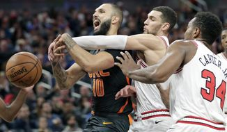 Orlando Magic guard Evan Fournier, left, is fouled as he goes up for a shot against Chicago Bulls guard Zach LaVine, center, and center Wendell Carter Jr. (34) during the second half of an NBA basketball game, Monday, Dec. 23, 2019, in Orlando, Fla. (AP Photo/John Raoux)