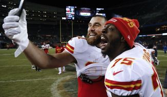 Kansas City Chiefs tight end Travis Kelce (87) and offensive tackle Cameron Erving (75) celebrate after beating the Chicago Bears 26-3 in an NFL football game in Chicago, Sunday, Dec. 22, 2019. (AP Photo/Charles Rex Arbogast)