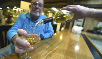 In this Nov. 25, 2019 photo, Alan Hargis has some wine poured for him at the Duplin Winery in Rose Hill, N.C. The winery has been around since the early 1970s. (Matt Born/The Star-News via AP)