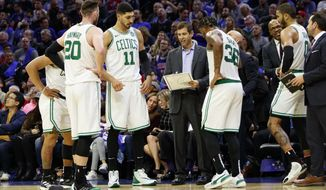 FILE- In this Oct. 23, 2019, file photo, Boston Celtics head coach Brad Stevens, center, talks things over with his team during the second half of an NBA basketball game against the Philadelphia 76ers in Philadelphia. Many coaches are striking the delicate balance between pushing inexperienced players enough for the players and the team to have success while realizing that the learning curve in the league is often a long one.  (AP Photo/Chris Szagola, File)