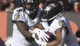 Baltimore Raven quarterback Lamar Jackson hands off to running back Mark Ingram during an NFL football game against the Cleveland Brown at FirstEnergy Stadium in Cleveland on Sunday, Dec. 22, 2019. (Warren Dillaway/The Star-Beacon via AP)