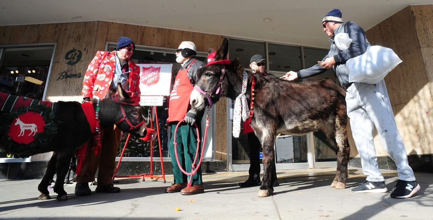 A pedestrian offers a donation to Salvation Army bell ringer John Maday, who was volunteering with Rich Kramer, center, and Neil Young, left, who brought his therapy donkeys in front of Boscov's on South Main Street in Wilkes-Barre, Pa., Thursday, Dec. 12, 2019. (Mark Moran/The Citizens' Voice via AP) ** FILE **
