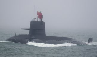 A Great Wall 236 submarine of the Chinese People's Liberation Army (PLA) Navy, billed by Chinese state media as a new type of conventional submarine, participates in a naval parade to commemorate the 70th anniversary of the founding of China's PLA Navy in the sea near Qingdao in eastern China's Shandong province, Tuesday, April 23, 2019. (AP Photo/Mark Schiefelbein, Pool)