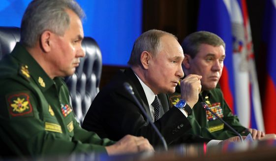 Russian President Vladimir Putin, center, gestures while speaking during an annual meeting with top military officials in the National Defense Control Center in Moscow, Russia, Tuesday, Dec. 24, 2019. Putin said that Russia is the only country in the world that has hypersonic weapons even though its military spending is a fraction of the U.S. military budget. Russian Defense Minister Sergei Shoigu, left, and Chief of General Staff of Russia Valery Gerasimov, right, attend the meeting. (Mikhail Klimentyev, Sputnik, Kremlin Pool Photo via AP)