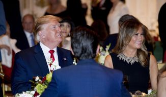 President Donald Trump and first lady Melania Trump attend Christmas Eve dinner at Mar-a-lago in Palm Beach, Fla., Tuesday, Dec. 24, 2019. Donald Trump Jr., the son of President Donald Trump, is pictured in foreground. (AP Photo/Andrew Harnik)