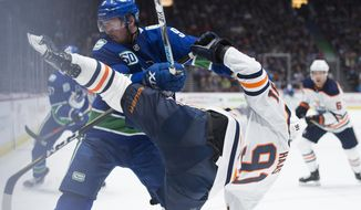 Vancouver Canucks center J.T. Miller (9) fights for control of the puck with Edmonton Oilers center Gaetan Haas (91) during the second period of an NHL hockey game Monday, Dec. 23, 2019, in Vancouver, British Columbia. (Jonathan Hayward/The Canadian Press via AP)