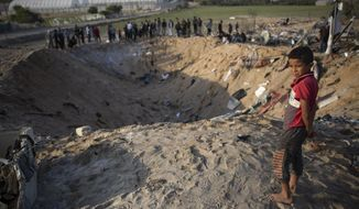 FILE - In this Nov. 14, 2019 file photo, a barefoot Palestinian boy looks into a crater made in an overnight Israeli missile strike, that destroyed a house and killed members of the Abu Malhous family, in Deir al-Balah, central Gaza. The Israeli military on Tuesday, Dec. 24, 2019 said it has wrapped up an investigation into the airstrike that killed nine Palestinian members of the Abu Malhous family in the Gaza Strip, claiming the house that was targeted had been used by Islamic militants but also admitting it did not expect the attack to result in civilian casualties. (AP Photo/Khalil Hamra, File)