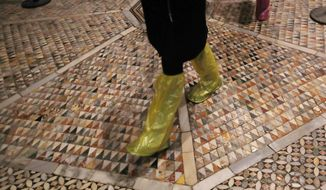 People walk on an interior mosaic floor of the St. Mark's Basilica in Venice, Italy, Tuesday, Dec. 17, 2019.  Still invisible to the naked eye and the casual visitors, recent flood damage to St. Mark's Cathedral in Venice has been put at 5 million euros (dollars U.S. 5.5 million), the damage is caused by salt which expands as it dries. (AP Photo/Antonio Calanni)