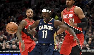 New Orleans Pelicans guard Jrue Holiday, center, loses control of the ball as Portland Trail Blazers guard Damian Lillard, left and center Hassan Whiteside, right, look on during the first half of an NBA basketball game in Portland, Ore., Monday, Dec. 23, 2019. The Blazers won 113-106. (AP Photo/Steve Dykes)
