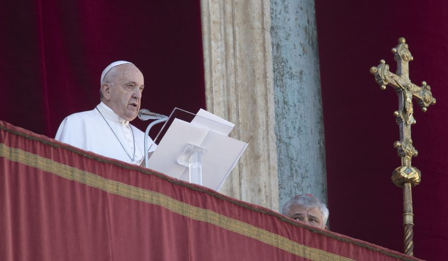 Pope Francis reads is message before delivering the Urbi et Orbi (Latin for 'to the city and to the world' ) Christmas' day blessing from the main balcony of St. Peter's Basilica at the Vatican, Wednesday, Dec. 25, 2019. At right is Cardinal Konrad Krajewski, the Vatican Almoner. (AP Photo/Alessandra Tarantino)