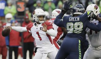 In this Sunday, Dec. 22, 2019, photo, Arizona Cardinals quarterback Kyler Murray passes as Seattle Seahawks defensive end Rasheem Green (98) applies pressure during the first half of an NFL football game in Seattle. Murray is short for an NFL quarterback at 5-foot-10, but it hasn't kept him from being very productive under first-year coach Kliff Kingsbury. Coaches and veteran players like receiver Larry Fitzgerald have raved about Murray's leadership, talent and toughness. (AP Photo/Elaine Thompson)