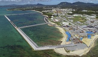 FILE - This Aug. 2018, file aerial photo shows preliminary construction work off Henoko, in Nago city, Okinawa prefecture, Japan, where the Japanese government plans to relocate a U.S. air base from one area of Okinawa's main island to another. A construction needed to improve the fragile structure underneath of a planned relocation site for a U.S. Marine Corps. base on Okinawa is to require twice as much time and cost than the previous estimate, adding more than a decade to the plan that has already been delayed for more than 20 years. The Defense Ministry on Wednesday, Dec. 25, 2019, said its latest estimate now shows that a relocation of the U.S. Marine Corps. (Koji Harada/Kyodo News via AP, File)