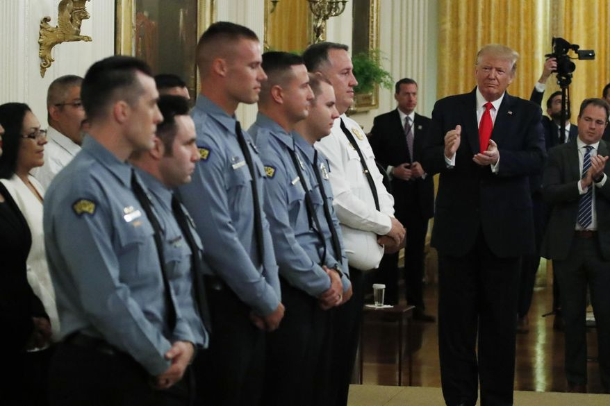 President Donald Trump applauds during a Medal of Valor and Heroic Commendations ceremony for six Dayton, Ohio police officers in the East Room of the White House in Washington.  (AP Photo/Alex Brandon, File)