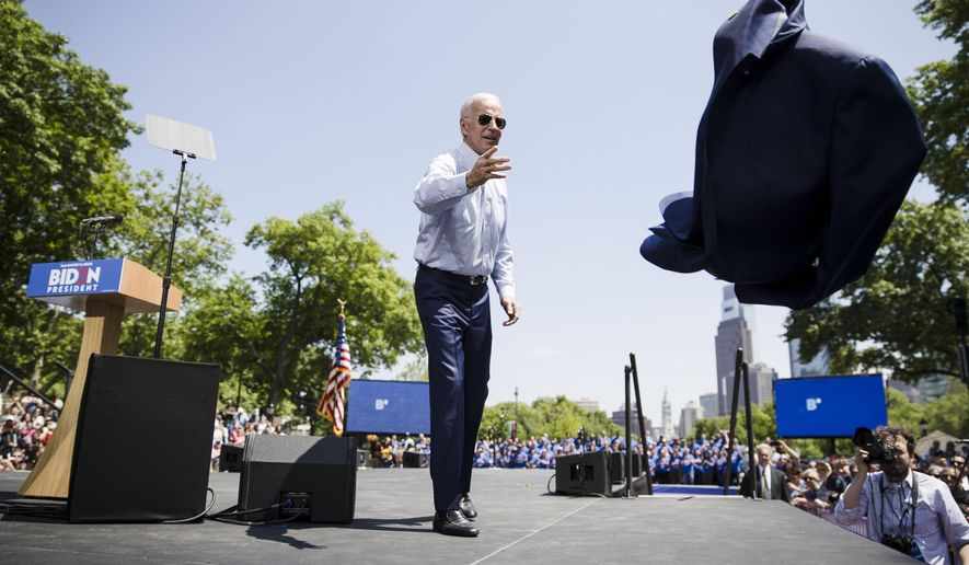 FILE - In this May 18, 2019 file photo, Democratic presidential candidate, former Vice President Joe Biden, tosses his coat during a campaign rally at Eakins Oval in Philadelphia. The 2020 presidential election campaign got underway as former vice president, and Scranton native, Biden launched his candidacy in Philadelphia. (AP Photo/Matt Rourke, File)