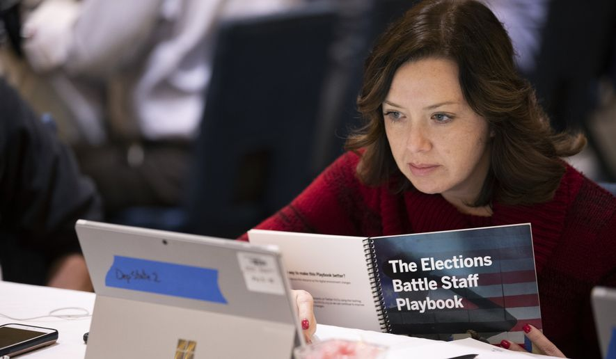 In this Monday, Dec. 16, 2019, photo, Mandy Vigil, from New Mexico, works during an exercise run by military and national security officials, for state and local election officials to simulate different scenarios for the 2020 elections, in Springfield, Va. These government officials are on the front lines of a different kind of high-stakes battlefield, one in which they are helping to defend American democracy by ensuring free and fair elections.  (AP Photo/Alex Brandon)