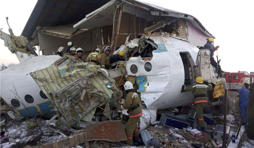 In this handout photo provided by the Emergency Situations Ministry of the Republic of Kazakhstan, police and rescuers work on the side of a plane crash near Almaty International Airport, outside Almaty, Kazakhstan, Friday, Dec. 27, 2019. Almaty International Airport said the Friday crash of a Bek Air plane in Kazakhstan has caused numerous deaths. The aircraft had 100 passengers and crew abroad, and hit a concrete fence and a two-story building shortly after takeoff. (Emergency Situations Ministry of the Republic of Kazakhstan photo via AP)