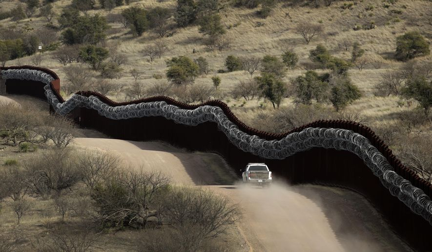 This March 2, 2019, file photo shows a Customs and Border Control agent patrols on the US side of a razor-wire-covered border wall along the Mexico east of Nogales, Ariz. (AP Photo/Charlie Riedel, File)