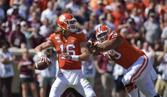 This Sept. 7, 2019, file photo shows Clemson quarterback Trevor Lawrence dropping back to pass with blocking help from Jackson Carman (79) during the second half of an NCAA college football game in Clemson, S.C. Carman is one of the few recent five-star recruits from Ohio who didn't end up at Ohio State. Now the two schools meet in the CFP semifinals, where Carman will be matched up against Ohio State's star defensive lineman Chase Young.  (AP Photo/Richard Shiro, File) **FILE**