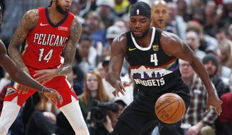 Denver Nuggets forward Paul Millsap, right, loses control of the ball as New Orleans Pelicans forward Brandon Ingram defends during the first half of an NBA basketball game Wednesday, Dec. 25, 2019, in Denver. (AP Photo/David Zalubowski)