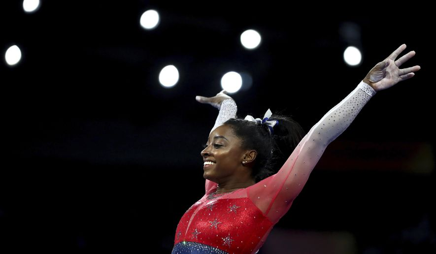 File-This Oct. 8, 2019, file photo shows Simone Biles of the U.S. performs on the vault during the women's team final at the Gymnastics World Championships in Stuttgart, Germany. Biles is the 2019 AP Female Athlete of the Year. She is the first gymnast to win the award twice and the first to win it in a non-Olympic year. (AP Photo/Matthias Schrader, File)