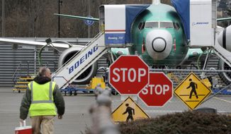 FILE - In this Monday, Dec. 16, 2019, file photo, a Boeing worker walks in view of a 737 MAX jet in Renton, Wash. Boeing announcing the halting of production of its troubled 737 Max airliner was voted Washington state's top news story of 2019 by Associated Press staff. (AP Photo/Elaine Thompson, File)