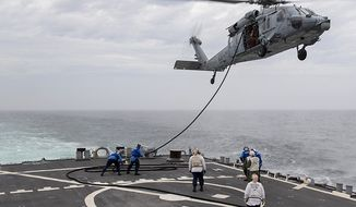 In this file photo, sailors aboard the Arleigh Burke-class guided-missile destroyer USS Gonzalez (DDG 66) fuel an MH-60S Knighthawk helicopter, attached to Helicopter Sea Combat Squadron (HSC) 7, Nov. 2, 2018. The U.S. Navy on Sept. 4, 2021, declared five missing sailors dead nearly a week after a similar helicopter crashed in the Pacific Ocean, shifting the search for them to a recovery operation on Saturday. (U.S. Navy photo by Mass Communication Specialist 2nd Class Tamara Vaughn/Released)  **FILE**