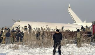 Police guard as rescuers work on the side of a plane crashed near Almaty International Airport, outside Almaty, Kazakhstan, Friday, Dec. 27, 2019. The Kazakhstan plane with 98 people aboard crashed shortly after takeoff early Friday. (AP Photo/Vladimir Tretyakov)