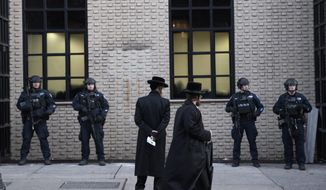 FILE - In this Dec. 11, 2019 file photo, Orthodox Jewish men pass New York City police guarding a Brooklyn synagogue prior to a funeral for Mosche Deutsch in New York. Deutsch, a rabbinical student from Brooklyn, was killed in the shooting inside a Jersey City, N.J. market. New York City is increasing its police presence in some Brooklyn neighborhoods with large Jewish populations after a number of possibly anti-Semitic attacks during the Hanukkah holiday. (AP Photo/Mark Lennihan, File)