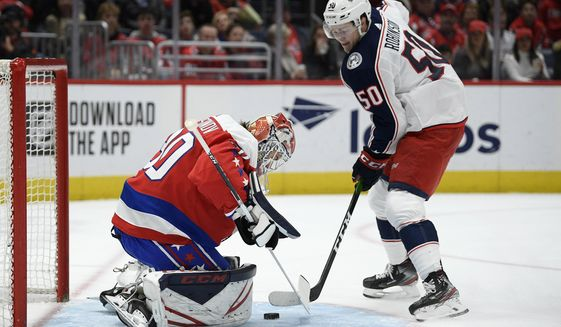 Washington Capitals goaltender Ilya Samsonov (30), of Russia, defends the net next to Columbus Blue Jackets left wing Eric Robinson (50) during the first period of an NHL hockey game Friday, Dec. 27, 2019, in Washington. (AP Photo/Nick Wass) ** FILE **