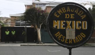 A sign announces Mexico's embassy where Bolivian police stand guard in La Paz, Bolivia, Thursday, Dec. 26, 2019. Mexico's Foreign Relations Secretary Marcelo Ebrard said the agents, who also stand around the Mexican ambassador's residence, appear to threaten Mexico's right to give asylum to nine former officials of ousted leader Evo Morales. (AP Photo/Luis Gandarillas)