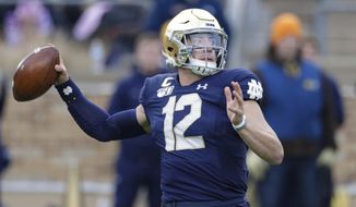 Notre Dame quarterback Ian Book (12) throws against Boston College during the first half of an NCAA college football game in South Bend, Ind., Saturday, Nov. 23, 2019. (AP Photo/Michael Conroy)