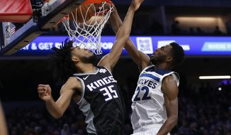 Minnesota Timberwolves forward Andrew Wiggins, right, stuffs over Sacramento Kings forward Marvin Bagley III during the first quarter of an NBA basketball game in Sacramento, Calif., Thursday, Dec. 26, 2019. (AP Photo/Rich Pedroncelli)