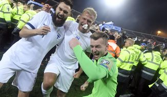Finnish captain Tim Sparv, left, celebrates with Paulus Arajuuri, center, and goalkeeper Lukas Hradecky after their victory in the Euro 2020 Group J qualifying soccer match between Finland and Liechtenstein in Helsinki, Finland, on Friday, Nov. 15, 2019. Finland won 3-0 and have qualified for a major soccer tournament for the first time in their history. (Markku Ulander/Lehtikuva via AP)