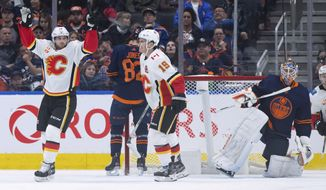 Calgary Flames' Elias Lindholm, left, of Sweden, and Matthew Tkachuk (19) celebrate Lindholm's goal against Edmonton Oilers goalie Mikko Koskinen, right, of Finland, during the second period of an NHL hockey game Friday, Dec. 27, 2019, in Edmonton, Alberta. (Darryl Dyck/The Canadian Press via AP)