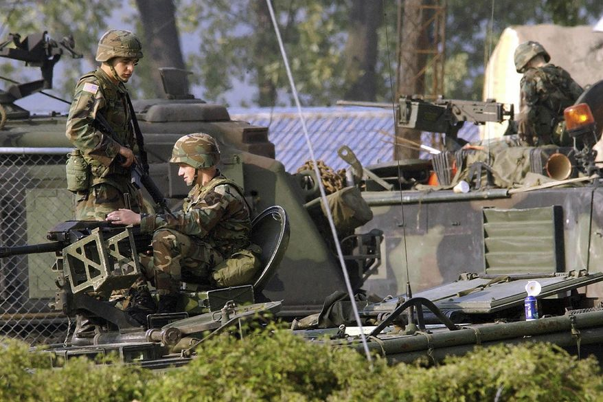 In this Oct. 6, 2004, file photo, U.S. Army soldiers stand guard on the armored vehicles at their base in Dongducheon, South Korea. (AP Photo/Ahn Young-joon, File)