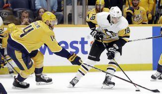 Nashville Predators defenseman Mattias Ekholm (14), of Sweden, tries to slow Pittsburgh Penguins center Alex Galchenyuk (18) during the first period of an NHL hockey game Friday, Dec. 27, 2019, in Nashville, Tenn. (AP Photo/Mark Humphrey)