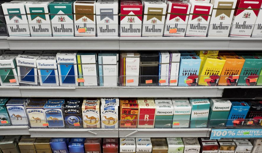 FILE - This Aug. 28, 2017 file photo shows cigarettes displayed on a store shelf in New York. With a new law enacted in December 2019, anyone under 21 can no longer legally buy cigarettes, cigars or any other tobacco products in the U.S. It also applies to electronic cigarettes and vaping products that heat a liquid containing nicotine. (AP Photo/Mark Lennihan, File)