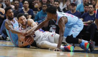 Philadelphia 76ers guard Ben Simmons, center, Miami Heat forwards Derrick Jones Jr., left, and Jimmy Butler, right, battle for the ball during the first half of an NBA basketball game, Saturday, Dec. 28, 2019, in Miami. (AP Photo/Wilfredo Lee)