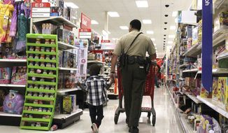 Ronquail Ollison Jr. (R.J.), a 5-year-old pre-K student at Truman Elementary shops with school resource officer Cpl. Thomas Babineaux at Target during the Shop with a Cop event on Dec. 23, 2019. (Ashley White/The Daily Advertiser via AP)