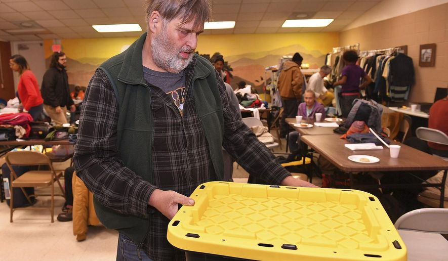 The Spartanburg Opportunity Center, a homeless day center which opened in August at the Northwest Community Center, served dozens Wednesday morning, December 11, 2019. The center provides homeless individuals with free clothes and food, phone charging, showers, and laundry. Andrew Stanga stores personal items in a storage box locker at the center Wednesday. (Tim Kimzey/Spartanburg Herald-Journal via AP)