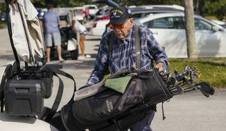 Julius Okrzesik, 99, unloads his golf clubs from the golf cart after playing a round of golf at the Bardmoor Golf and Tennis Club on Tuesday, Nov. 26, 2019 in Seminole, Fla.(Martha Asencio Rhine/Tampa Bay Times via AP)
