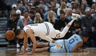 Denver Nuggets forward Michael Porter Jr., front, loses control of the ball and his footing after colliding with Memphis Grizzlies guard De'Anthony Melton in the first half of an NBA basketball game Saturday, Dec. 28, 2019, in Denver. (AP Photo/David Zalubowski)