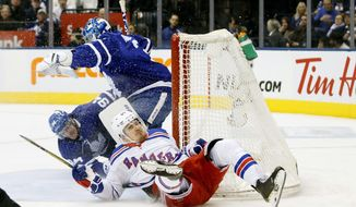 New York Rangers right wing Pavel Buchnevich (89) crashes into Toronto Maple Leafs goaltender Frederik Andersen (31) and the net with Maple Leafs defenseman Tyson Barrie (94) during first-period NHL hockey game action in Toronto, Saturday, Dec. 28, 2019. (Cole Burston/The Canadian Press via AP)