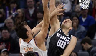 Phoenix Suns forward Dario Saric, center, goes to the basket against Sacramento Kings forward Nemanja Bjelica, right, during the first quarter of an NBA basketball game in Sacramento, Calif., Saturday, Dec. 28, 2019. (AP Photo/Hector Amezcua)