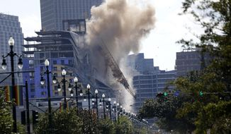 FILE - In this Oct. 20, 2019 file photo, two large cranes from the Hard Rock Hotel construction collapse come crashing down after being detonated for implosion in New Orleans. New Orleans officials set off several explosions Sunday intended to topple two cranes that had been looming over the ruins of a partially collapsed Hard Rock Hotel, that had been under construction. (AP Photo/Gerald Herbert, File)
