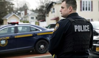 A Ramapo police officer directs traffic outside a rabbi's residence in Monsey, N.Y., Sunday, Dec. 29, 2019, following a stabbing at the home Saturday night during a Hannukah celebration. (AP Photo/Julius Constantine Motal)